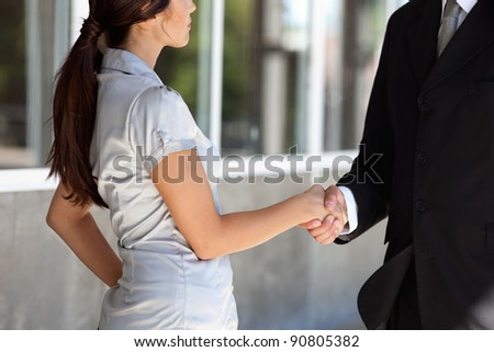 Faceless professional businesspeople shaking hands