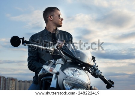Faceman on the beach with his sport-bike at sunset - stock photo