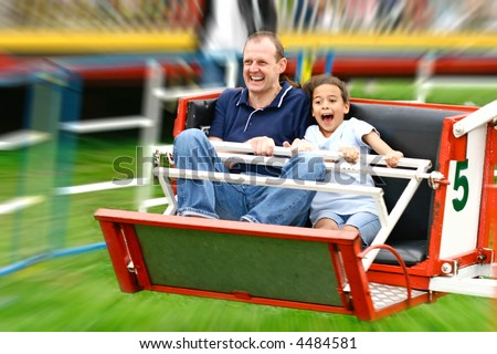 Faces of excitement from a father and daughter as they enjoy the fast octopus ride in the park - stock photo