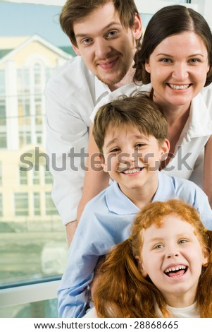 Faces of happy family members looking at camera and laughing - stock photo