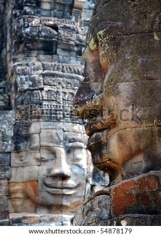 Faces of King Yayavarmann VII on the beautiful Bayon temple, Angkor Wat, Cambodia - stock photo
