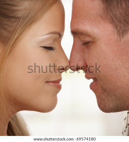 Faces of loving couple with eyes closed in closeup, touching noses.? - stock photo