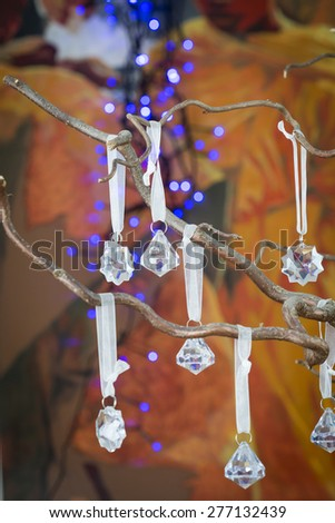 Faceted crystal Christmas decorations shaped as droplets and stars or snowflakes hanging on the dried branches of a modern Christmas tree to celebrate the festive season, close up background view - stock photo