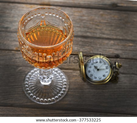 Faceted glass of whisky and Vintage pocket watch on wooden texture
