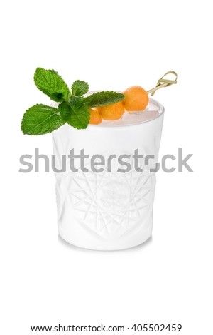 Faceted white cocktail glass decorated with melon on stick and mint leaves - stock photo