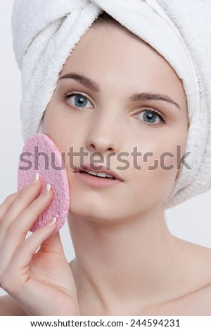 Facial beauty portrait of blue-eyed young lady with natural make-up, french manicure  and clean skin with white towel on her head and pink rough sponge in her left hand closing her left cheek. - stock photo
