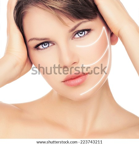 Facial care and treatment. Close-up portrait of beautiful female with laser lines on her face. Young attractive Caucasian woman with perfect healthy skin.  - stock photo