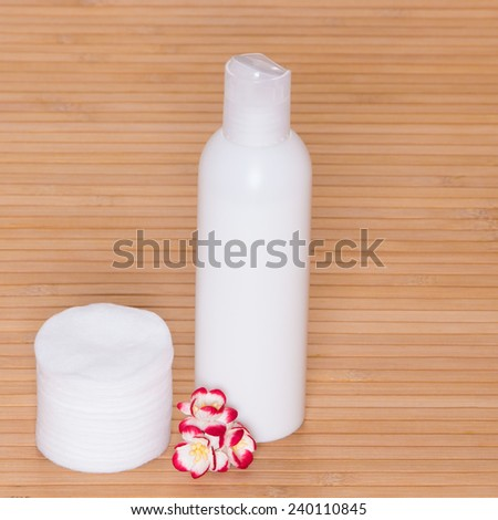 Facial cleaning and makeup removing cosmetic product with  cotton pads and small flowers on wooden surface - stock photo