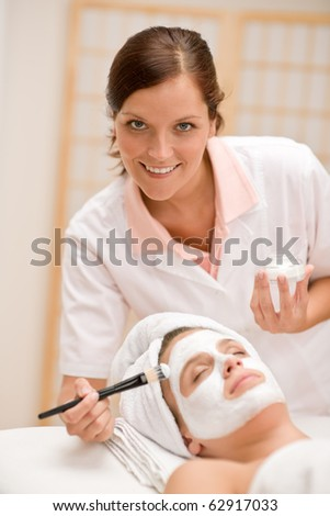 Facial mask - woman at beauty salon getting treatment - stock photo
