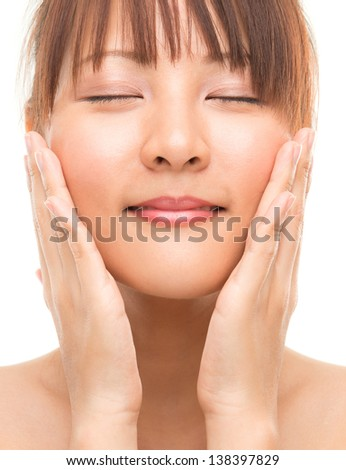 Facial massage. Asian skincare woman pampering face skin, skin care refreshing concept. Facial close up of beautiful mixed race Asian. Girl isolated on white background - stock photo