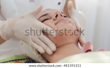 Facial massage,cosmetician woman makes facial massage with oil