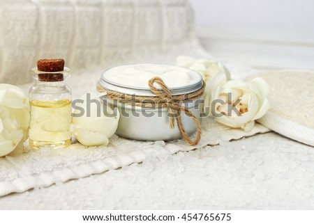 Facial natural cream container, fresh beige garden roses, aroma essential oil, white towel. - stock photo