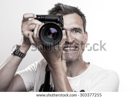 Facial of a photographer holding a camera in his hands looking at you