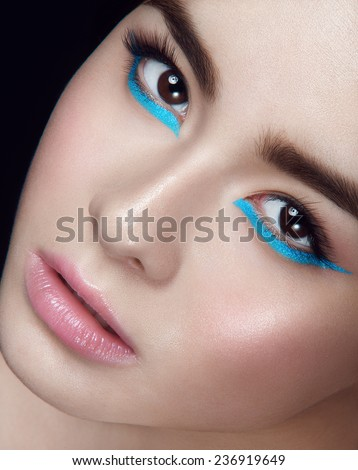 Facial portrait of asian young girl with blue wings under hazel eyes and open lips looking at you with head to the right on black background - stock photo
