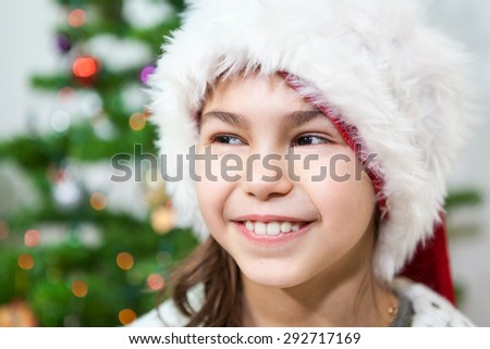 Facial portrait of young smiling happy girl in white Santa hat - stock photo