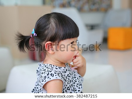 facing side baby girl finger sucking mouth - stock photo
