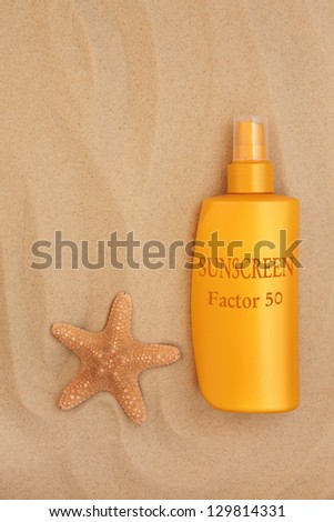 Factor fifty sunscreen bottle with starfish shell over sand background. - stock photo