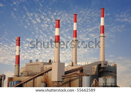 Factory against blue cloudy sky - stock photo