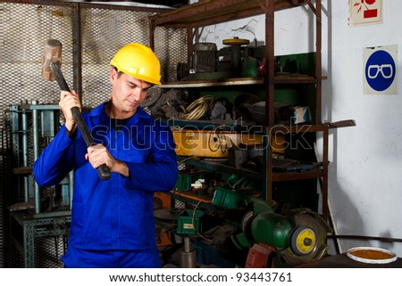 factory blue collar worker using big hammer in workshop - stock photo