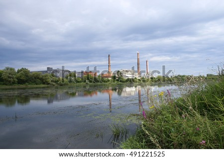 Factory by the river. Industrial landscape in East Europe.