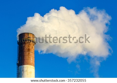 factory chimney and coming out white smokes in the blue sky background - stock photo