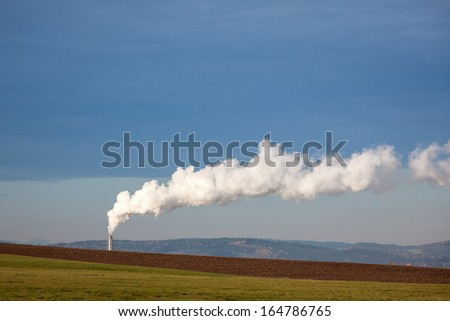 Factory chimney polluting the air in clean landscape - stock photo
