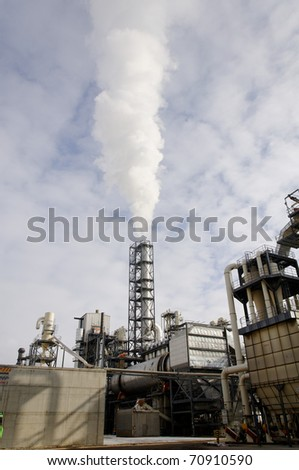 Factory chimney poluting air - stock photo