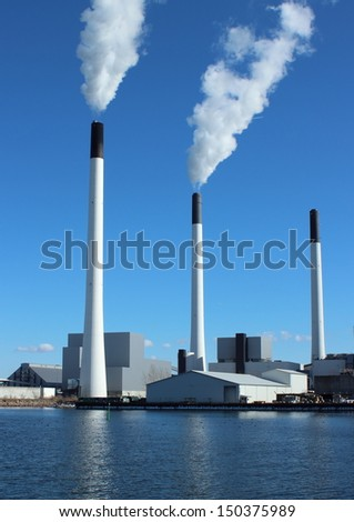 Factory chimneys at energy plant with blue sky and lake. Focus on a global green environment, and a healthy surrounding.