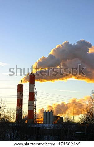 Factory chimneys smoke rising into the sky at sunset