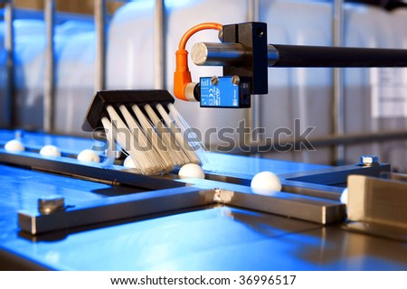 Factory cleaning and filling machine for bug spray balls - stock photo