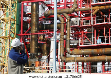 factory constructions with site worker talking in phone - stock photo