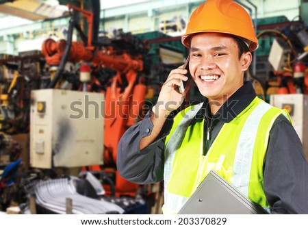 Factory engineer standing beside robot machine doing conversation on the phone - stock photo