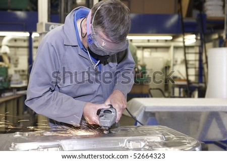 factory floor worker using a angle grinder on metal surface