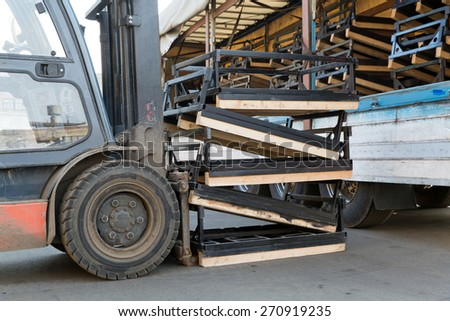 Factory Forklift Stacker loading Cargo into Truck Trailer - stock photo