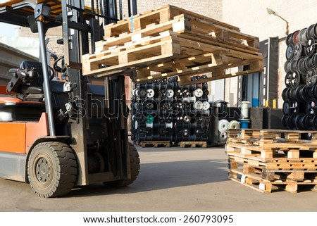 Factory Forklift Truck Stacker Transporting Pallets at Plant Warehouse - stock photo