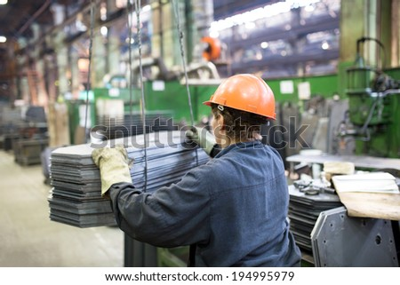 Factory Industrial Worker transporting cargo with workshop crane - stock photo