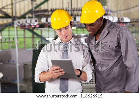 factory manager and worker looking at tablet computer - stock photo