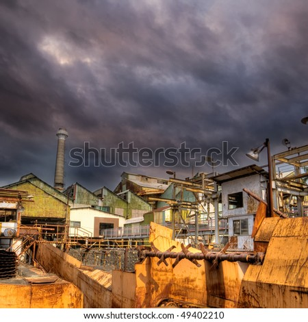 Factory of abandonment with dramatic cloud in sky.