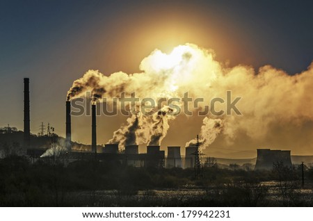 Factory pipe polluting air, smoke from chimneys against sun, environmental problems, ecological theme, industry scene - stock photo