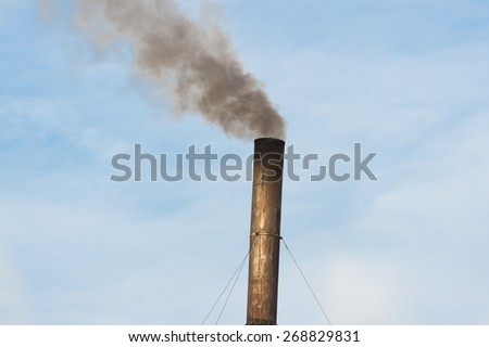 Factory plant with balck smoke and blue sky - stock photo