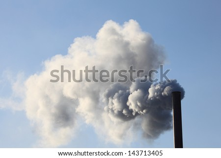 Factory smokestack blowing fume into the atmosphere
