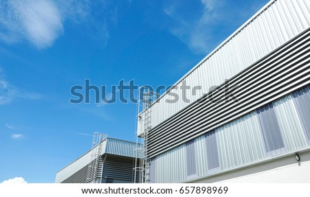 Factory warehouse and industrial concept - Wall and roof of Factory or warehouse building in industrial estate with blue sky and copyspace