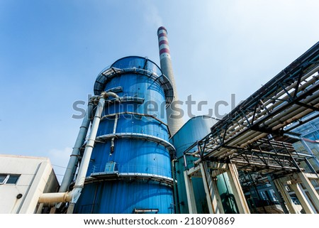 factory with main chimneys expelling smoke into a deep blue sky - stock photo