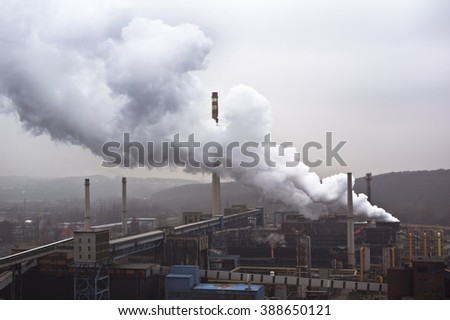 Factory with many smokestacks and big smoke as symbol of air pollution and environment problematic (used dim exposure to highlight negativity) - stock photo