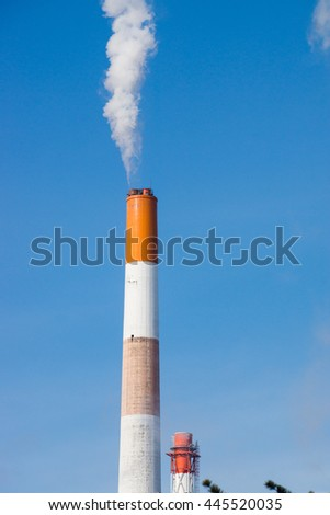 Factory with smokestack pulling out toxic steam - stock photo