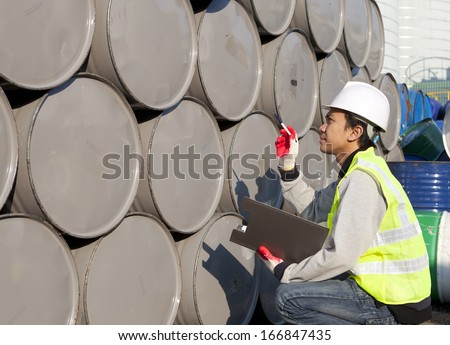 Factory worker calculate of drums - stock photo