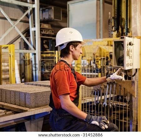 Factory worker fixing broken device - stock photo