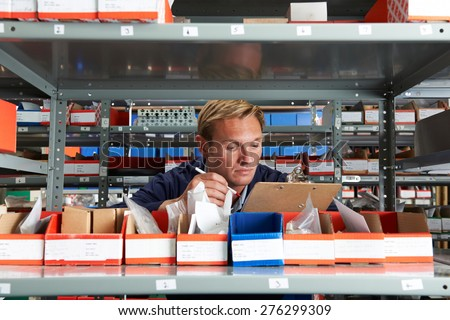 Factory Worker In Store Room Checking Stock - stock photo