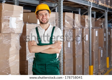 Factory worker in warehouse with founded hands - stock photo