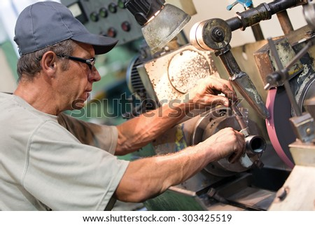 Factory worker measure detail with digital caliper micrometer during finishing metal working on lathe grinder machine - stock photo